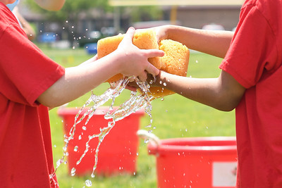 First graders pass water-filled sponges during the Sponge Relay at Antrim Elementary's Field Day on June 6, 2019. [ALYSSA RASP   THE OCEAN STAR]