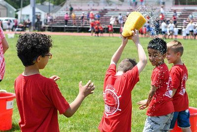First graders pass water-filled sponges during the Sponge Relay at Antrim Elementary's Field Day on June 6, 2019. [ALYSSA RASP | THE OCEAN STAR]