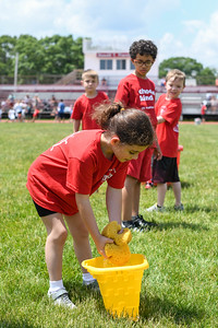 First graders squeeze out water-filled sponges during the Sponge Relay at Antrim Elementary's Field Day on June 6, 2019. [ALYSSA RASP | THE OCEAN STAR]