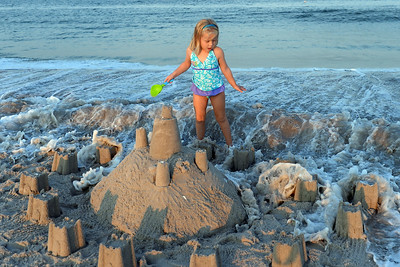 4 year old Samantha Newman gets surprised by a big wave while attending to her sand castle at the Kites and Castles event on Lavallette Beach, in Lavallette, NJ on 08/01/2019. (STEVE WEXLER/THE OCEAN STAR).