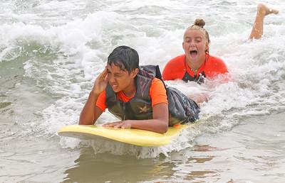 Beach surfer, Ella Betten, surfing with Christian Gamble. The Point Pleasant Beach surf team at the POAC event in Island Beach State Park, NJ on 8/8/19. [DANIELLA HEMINGHAUS]