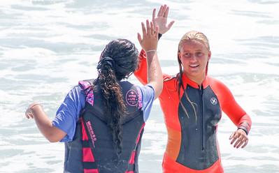 Emily Kolchin, from Lanoka Harbor, hifiving surfer Ella Betten. The Point Pleasant Beach surf team at the POAC event in Island Beach State Park, NJ on 8/8/19. [DANIELLA HEMINGHAUS]
