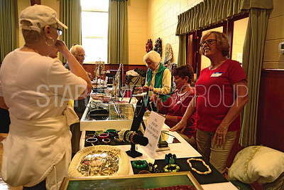 on right- pat tissot of brick helping a woman pick out jewlery