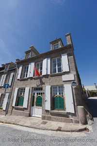 BARFLEUR, FRANCE - JULY 4: Medieval granite house with Normandy flag in Barfleur, France on July 4, 2011. Barfleur is a picturesque fishing village on the peninsula Cotentin in Basse Normandy.
