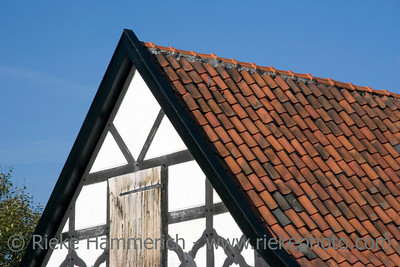 gable of a half-timbered house in black and white with red tiles - in a traditional german village
