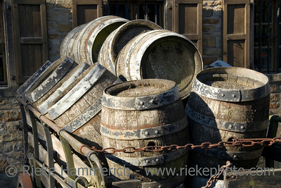 antique beer barrels - draft beer on a hay cart in front of the brewery