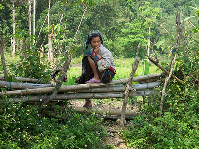 A young Bru girl sitting on a fence near Hill 881 South.