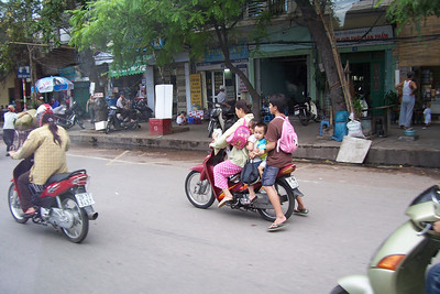 In Ha Noi, we spot a family of five on one motorbike.  The legal limit in Vietnam is three to a bike and adults must wear a helmet............ So much for rules.
