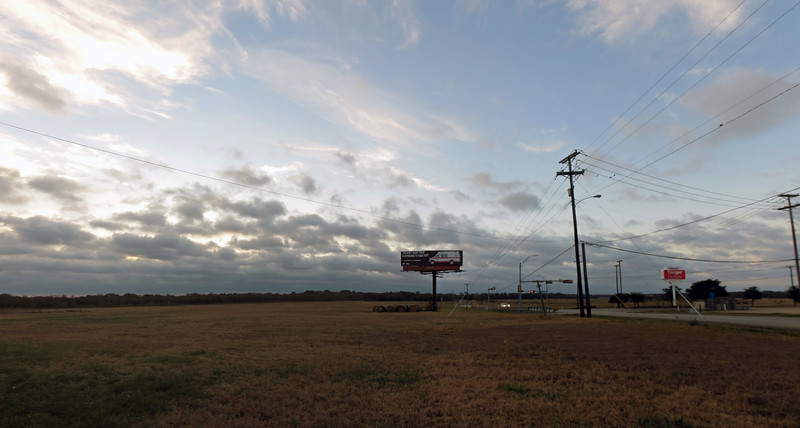 Three-picture panorama of the large open field next to the Super 8 hotel.