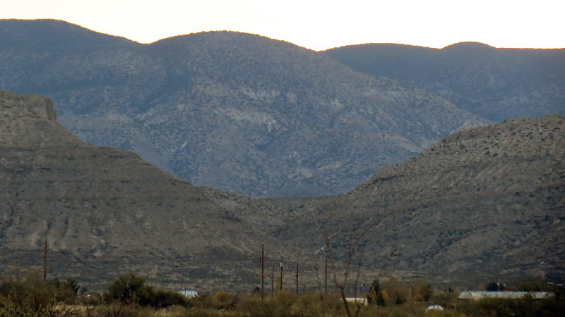 Gap in between a pair of 5,600-foot peaks in front of several 8,000-foot peaks of the Sacramento Mountains, Tularosa, NM.