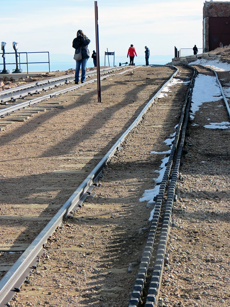 """The summit sign is located above the end of the tracks for the Cog Railway, which was closed for the season during our visit.  The railway uses standard gauge track with 4 ft 8 ½ in spacing between the outside rails.  The center rails with teeth mesh with a toothed wheel on the locomotive that allows the train to climb steep inclines, which is definitely the case here.  The average grade of the 9-mile trip is 12% with a maximum of 24% in spots !  From what I read, this is the highest railway in North America.<br /> <br /> I also discovered while doing research for this write-up that the Cog Railway, which was closed during our visit, will not be reopening anytime soon.  The railway was closed so maintenance could be performed during the winter, during which time several issues with the integrity of the line were discovered.  According to the company website, the railway will remained closed, """"for the foreseeable future."""""""
