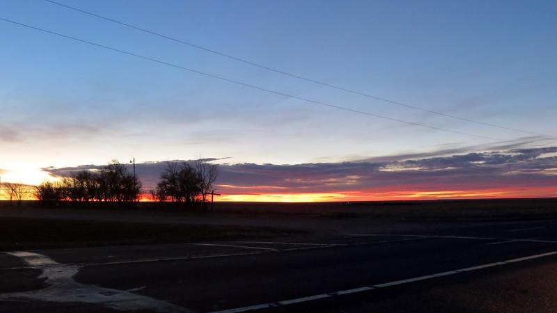 Three-picture panorama of sunrise in Woodrow, Colorado.