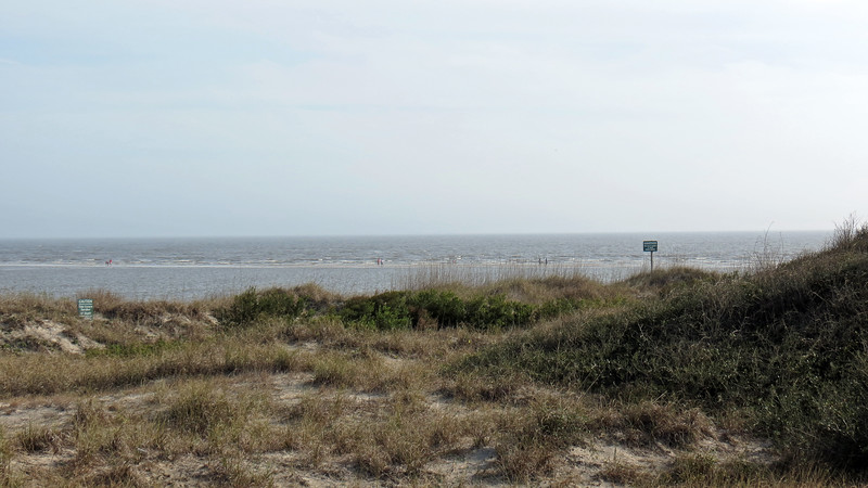 The sandbar and all the people walking on it could be seen from the parking lot at low tide.