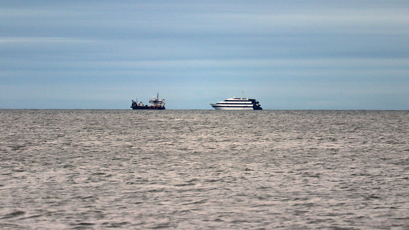 The ship on the left in the photo above looks like a bulk carrier of some kind.  The ship on the right resembles the nearby Emerald Princess Casino ship.