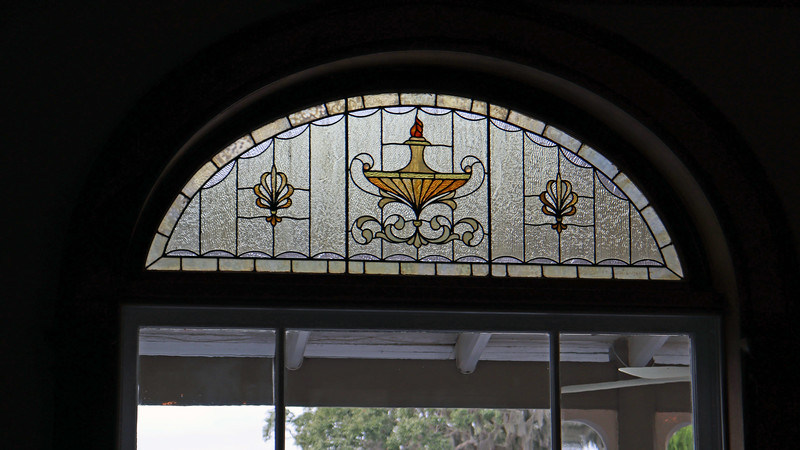This stained glass window looks out over the large porch and the pool.