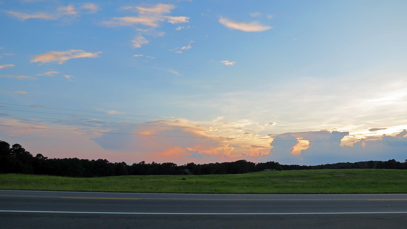 The large open field across the street provided unobstructed views of the clouds and sunset.