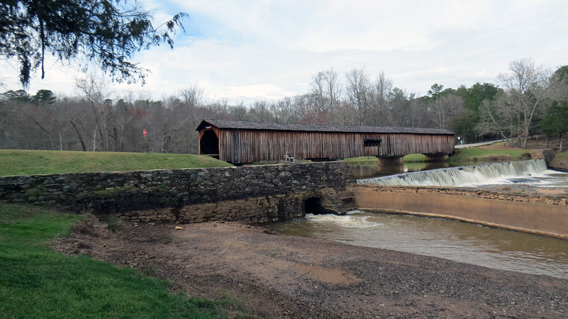 The story of the Watson Mill Bridge begins in 1868 when Gabriel Watson purchased a grist mill and sawmill that were located on this site.  The grist mill was originally built around 1798 and was successful to the point that a small community had developed around it.  The mill was powered by a water wheel driven by water from the South Fork of the Broad River.<br /> <br /> Washington W. King, son of well known bridge builder and freed slave Horace King, was called upon to build a bridge over the river to provide access to the mills and surrounding community.  King built a 229-foot Town Lattice bridge, (held together by wooden pins), in 1885.