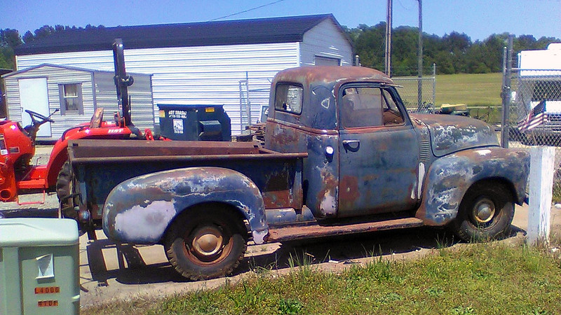 """I'm not certain of the year of this truck.  But there are a few distinct clues.  The Advance Design series of trucks was introduced for the 1948 model year.  The fuel cap on this truck is located on the cab behind the door handle which means it's not a 1948 model.  The doors have vent windows which were introduced for the 1951 model year.  The door handles have push buttons, (instead of a rotating handle assembly), which were introduced for 1952.  And the windshield is still the old 2-piece design, (a 1-piece curved windshield was introduced for 1954).  So this truck is either a 1952 or 1953 Chevrolet 3100 Series pickup, with """"3100"""" designating the half-ton model.<br /> <br /> This one looks like it's been sitting for a while, and would be an intense project.  But it seems complete, overall.  Parts support for these trucks is quite good.  And as long as the frame doesn't look like Swiss cheese, someone with the right skills could have a great project."""