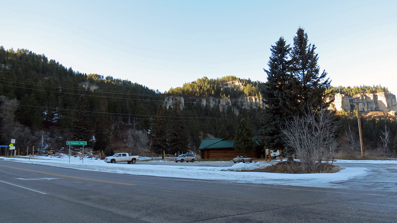 The photo above looks back on the Spearfish Falls parking area.  The building with the green roof is the Latchstring Restaurant.  <br /> <br /> Nobody paid much attention to Spearfish Canyon until gold was discovered here in 1876.  That brought mining operations to the area along with logging and sawmills.  The railroad arrived in 1893.  The area was designated a Forest Reserve in 1897 and a National Forest in 1905.  With that designation came tourists.  The Latchstring Restaurant of today began life as the Glendoris Lodge which opened in 1906.  In 1919, it was renamed the Latchstring Inn.  The original building was replaced in 1989 with the current building seen in the photo.