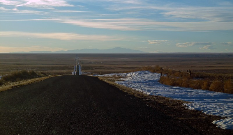 """Wide open spaces are plentiful once you get outside of the major city limits.  But extremely rural areas in the eastern part of the state take the definition of """"wide open spaces"""" to a whole other level.  Heather took the photo above while traveling on an isolated county road outside of Karval, Colorado.  Pikes Peak can be seen off in the distance."""