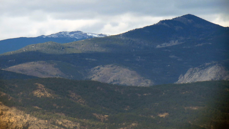 I zoomed in on the left side of the previous photo to get a perspective shot.  I think the snow capped peaks in the background on the left side of the photo below are the previously mentioned Stormy Peaks East (12,020 ft), and Stormy Peaks West (12,148 ft).  The pointed peak on the right is possibly Storm Mountain (9,918 ft).  The camera can't do justice to the scale of what I'm seeing.  Those tiny looking evergreen trees seen off in the distance on the side of the mountains are probably 25 - 50 feet tall !
