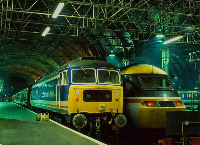 47579 having brought in the ECS for 1C02, the 00:05 sleeper to Penzance, <br /> stands alongside 43125 at Paddington on 8th June 1990.
