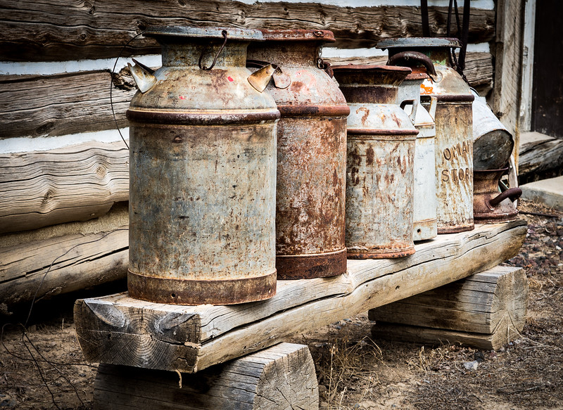 Antique Milk Cans on an Old Wooden Bench