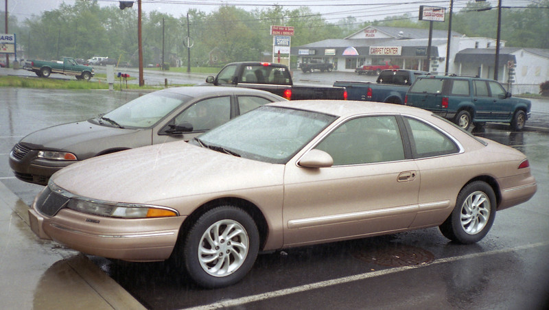 June 7, 2003:  I picked up this 61k original mile 1996 Lincoln Mark VIII from a customer at Bedford Ford.  I had serviced this car several times over the years, and even installed a new oil pan not too long before this photo was taken.  We met at Dunkle Services in Bedford, PA on this rainy Saturday morning to sign the paperwork.