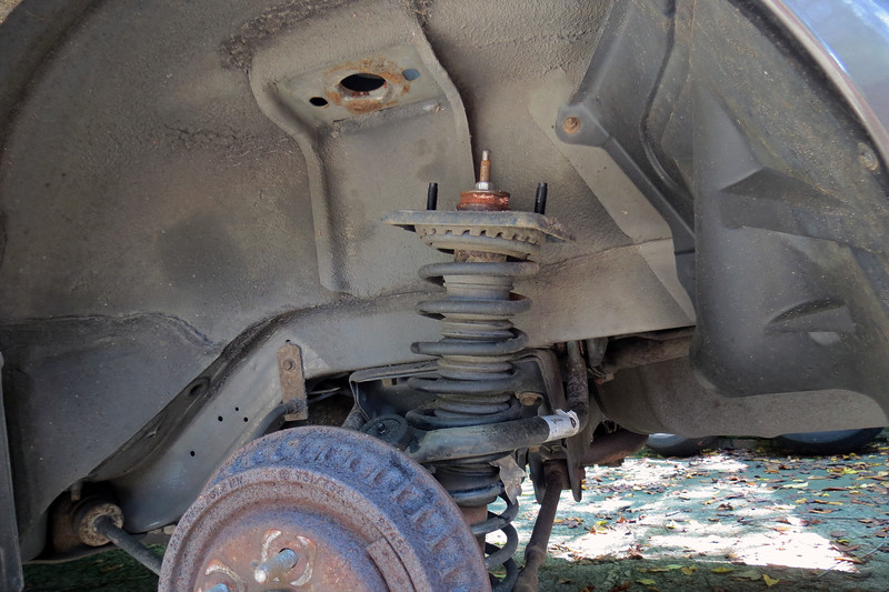 With the fasteners removed, the strut lowers from the body of the car, and can then be tilted for removal.