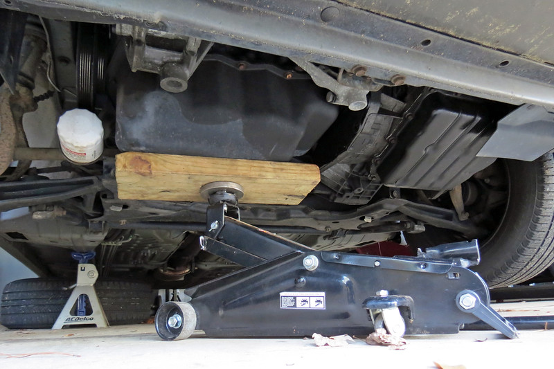 Since I'm trying to remove one of the engine mounts, I will need to support the engine from underneath.  My floor jack and a block of wood did the trick.