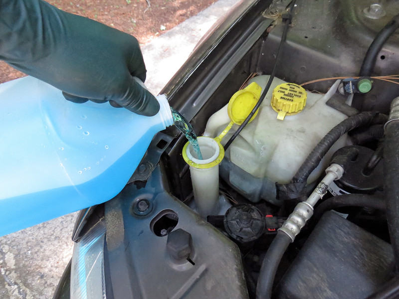 Adding washer fluid to the reservoir.