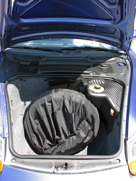 The rear compartment is complimented by a larger luggage compartment under the hood.  Engineers made the most of what they had to work with by mounting the spare tire vertically.  This makes the compartment especially deep, and more able to accommodate larger items.