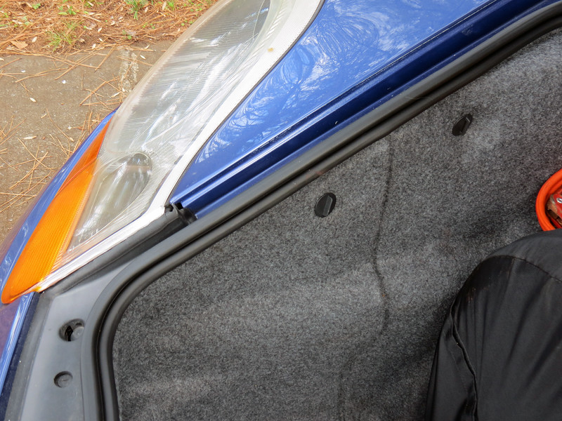 The headlamp assembly must be removed to gain access to the bulb.  It may sound menacing, but is actually quite simple.  The fastener that holds the assembly in place is accessed behind the trim in the front luggage compartment.