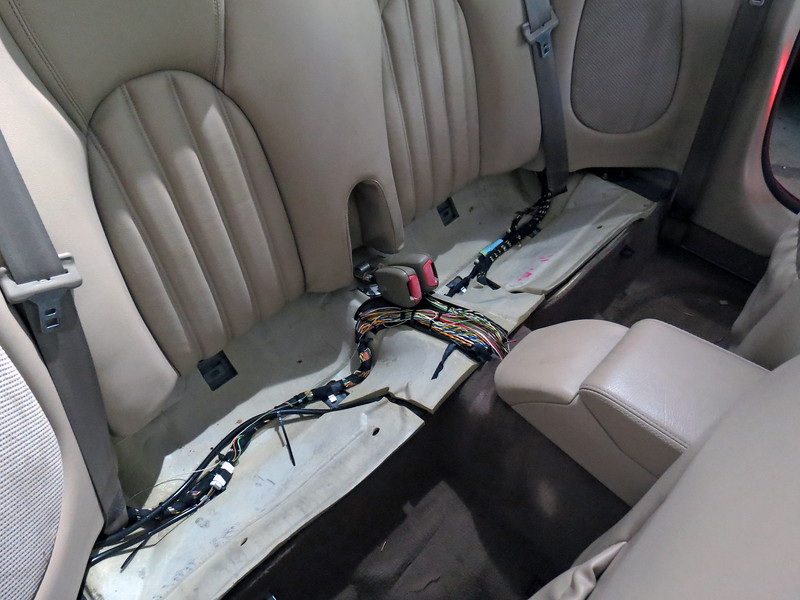 Remove the rear seat cushion:  It unbolts and lifts upward.