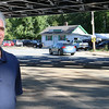 Bill Quirk watches as cars speed by under the bridge in front of his car dealership, in the background, on Tuesday afternoon in Frichburg. The state has been working on the bridge for over a year so River Street in front of his shop has been closed. SENTINEL & ENTERPRISE/JOHN LOVE