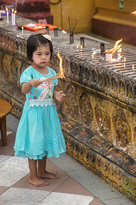Lighting candles around the main shrine at the Shwedagon Pagoda, Yangon, Myanmar.