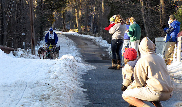 Spectators watch a team approach teh bridge on Cutler Road during the Myopia Sled Dog races Saturday. Dan Ryan/Staff photo.