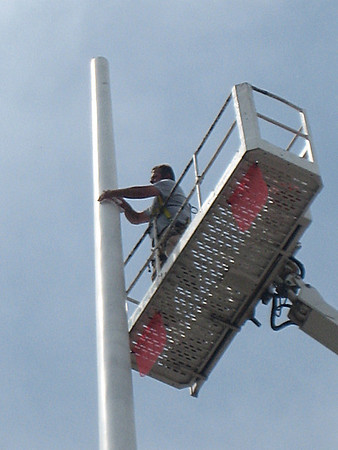 "DANVERS: A worker for Witch City Roofing of Salem fixes the 100-foot flagpole in Danvers Square on Wednesday. The worker was replacing the bucket-shaped ""truck"" at the top of the pole that spools a 216-foot stainless steel cable used to raise and lower the town's 25-foot-by-16-foot flag. The work was scheduled to be done so the flag could be back in the Square by Memorial Day."