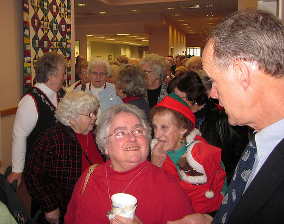 DANVERS: Town Manager Wayne Marquis, right, greets seniors, including Marlene Norton, center, as they head into a Christmas party luncheon at the Senior Center on Stone Street on Friday. About 130 seniors attended the gathering organized by Senior Center staff. Ethan Forman/staff photographer Dec. 16, 2011