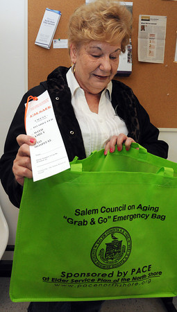 "Salem:<br /> Loretta Carroll looks into her ""grab and go"" emergency kit. Salem's Council on Aging, Board of Health and police and fire departments are collaborating to give away ""grab and go"" emergency kits to seniors in Salem. <br /> Photo by Ken Yuszkus/The Salem News, Thursday, April 11, 2013."