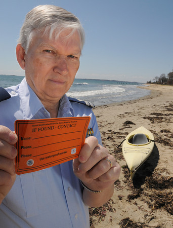 Beverly:<br /> Phil Karwowski of the U.S. Coast Guard Auxiliary, holds an identification sticker for unregistered watercraft. The Coast Guard has started a new program asking people to put identifying stickers on their kayaks, canoes, paddleboards and other unregistered watercraft so they can determine if they need to launch a search-and-rescue mission if they discover one of the crafts adrift. He is at West Beach in Beverly.<br /> Photo by Ken Yuszkus/The Salem News, Friday, April 26, 2013.