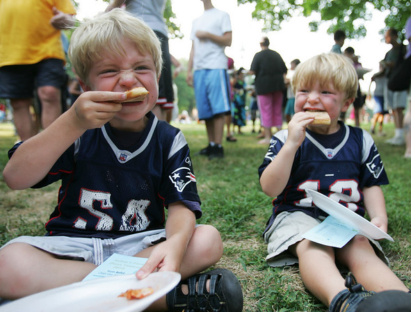 Brothers, Brewster Smyers, 5, and Whitman, 3, of Marblehead take a big bite out of their pizza during the Heritage Days Pizza Competition held at the Salem Common Monday evening. Photo by Deborah Parker/August 9, 2010