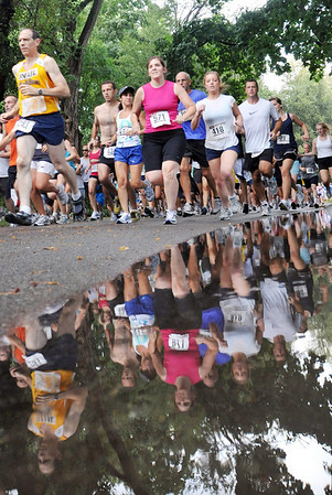 Athletes fly past puddles left by heavy rains which stopped in time for the road race.   photo by Mark Teiwes / Salem News