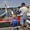 Markis Vigeant, 6, and his grandfather Dave Deinstadt, captain of the Jennifer Anne, size up the competition prior the annual Lobster Boat Races.  Photo by Mark Teiwes / Salem News