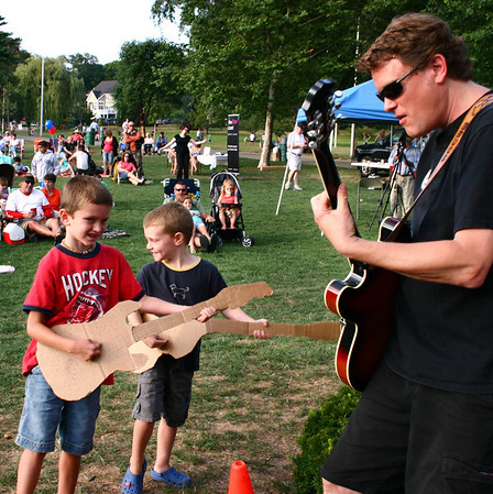 """Bobby Ring, 7, at left, and his brother Thomas, 5, jam on their cardboard guitars along with """"All Together Now"""" guitarist Bruce Hilton during the first weekend of the Beverly Homecoming festival in Lynch Park. Photo by Mary Catherine Adams/Salem News."""