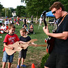 "Bobby Ring, 7, at left, and his brother Thomas, 5, jam on their cardboard guitars along with ""All Together Now"" guitarist Bruce Hilton during the first weekend of the Beverly Homecoming festival in Lynch Park. Photo by Mary Catherine Adams/Salem News."