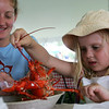Christina Zoba of Beverly helps Elizabeth Champagne, 5, of Beverly, examine her lobster before digging in while at the Lobster Festival part of this year's Beverly Homecoming. photo by Deborah parker/august 4, 2010