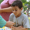 Alex Gallucci, age 6 of Beverly, waits while one of the volunteers at the Beverly Homecoming Ice Cream Social scoops some sprinkles onto his ice cream. The Cove Community Center lawn and parking lot were filled by hungry Beverly residents on a beautiful Monday afternoon. Photo by David Le/Salem News