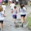 One runner chose to race through the puddles.    photo by Mark Teiwes / Salem News
