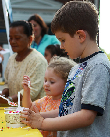 Jack Adams, age 5 right, and his sister Grace Adams, 3, watch closely and wait patiently while a volunteer at the Beverly Homecoming Ice Cream Social piles sprinkles on top of their ice creams. Photo by David Le/Salem News
